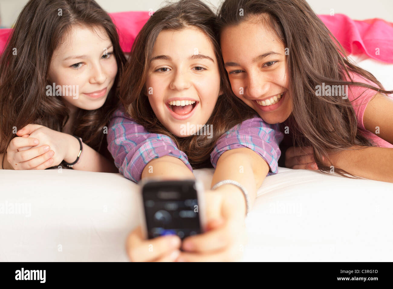 teenage girls taking photos wearing pajamas - Stock Image