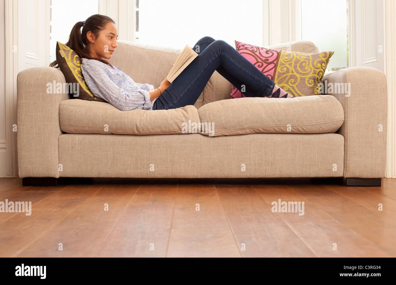 Teenage Girl Reading On Sofa   Stock Image