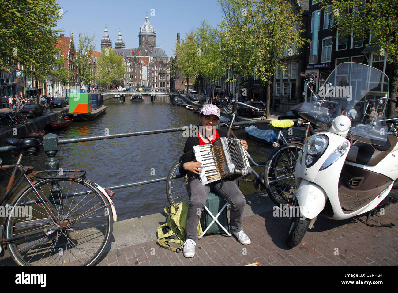 ACCORDION PLAYER & ST. NICHOLAS CATHEDRAL FROM LIESDELSLUIS BRIDGE AMSTERDAM 23 April 2011 - Stock Image