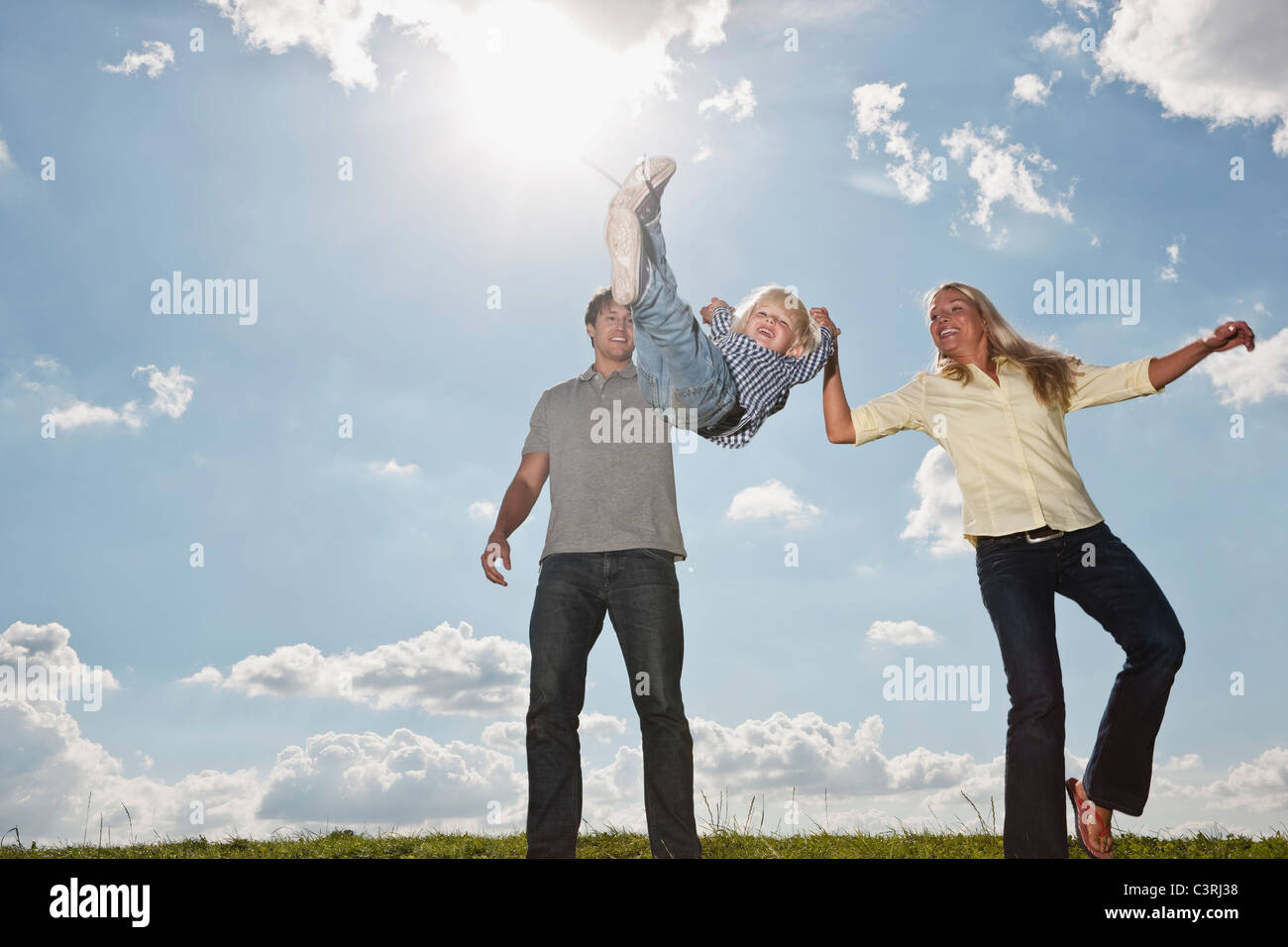 Germany, Cologne, Parents playing with their son (2-3 Years), smiling - Stock Image