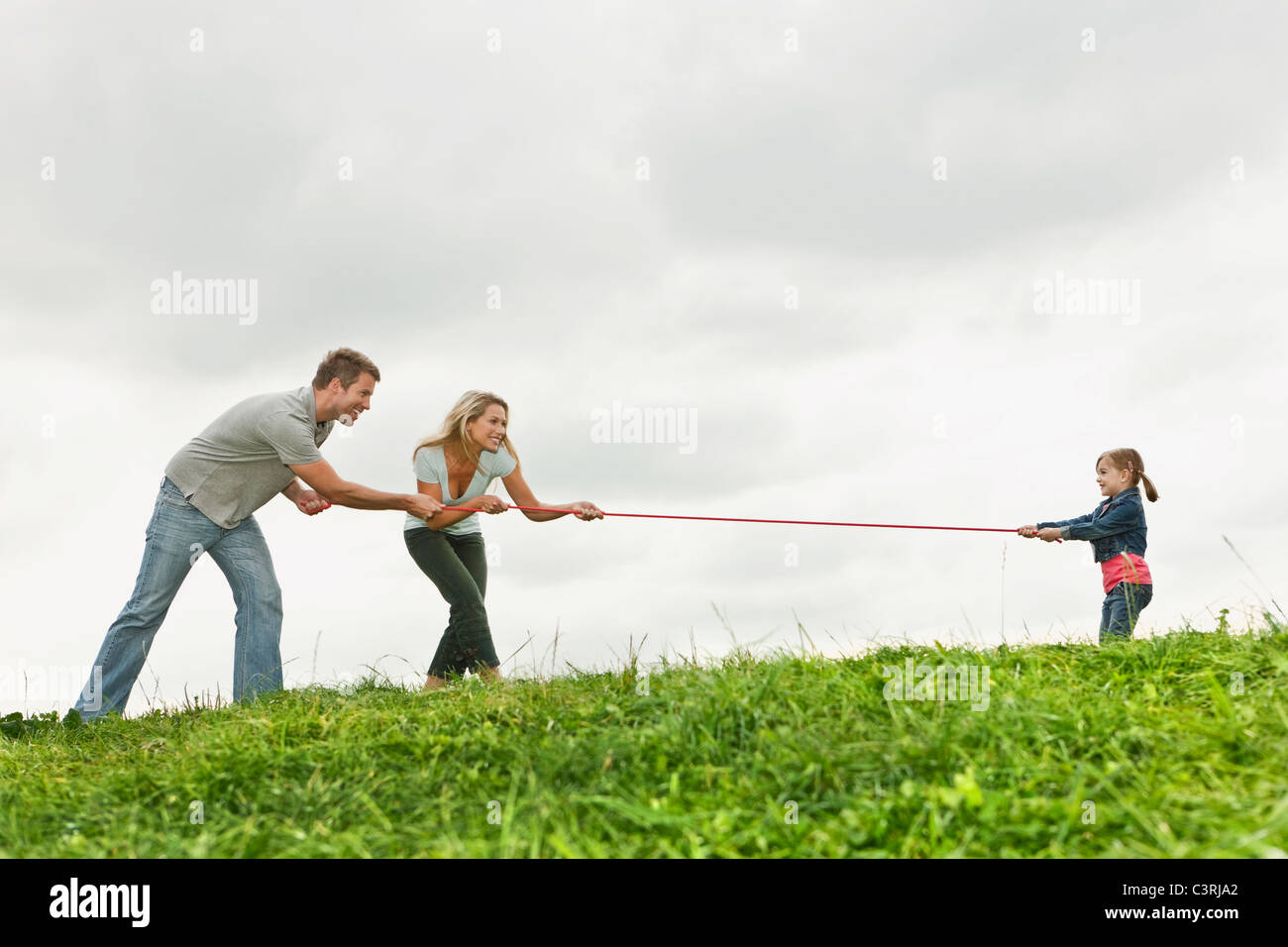 Germany, Cologne, Parents playing tug of war with girl (2-3 Years) - Stock Image