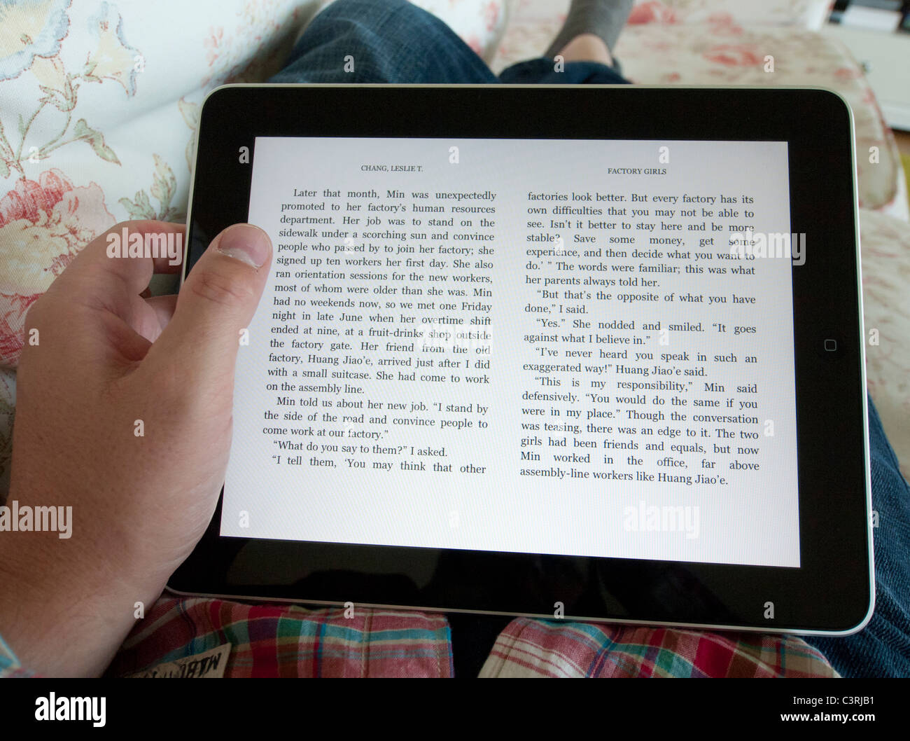 Man reading digital e-book using Amazon Kindle app on an iPad touch screen tablet computer - Stock Image