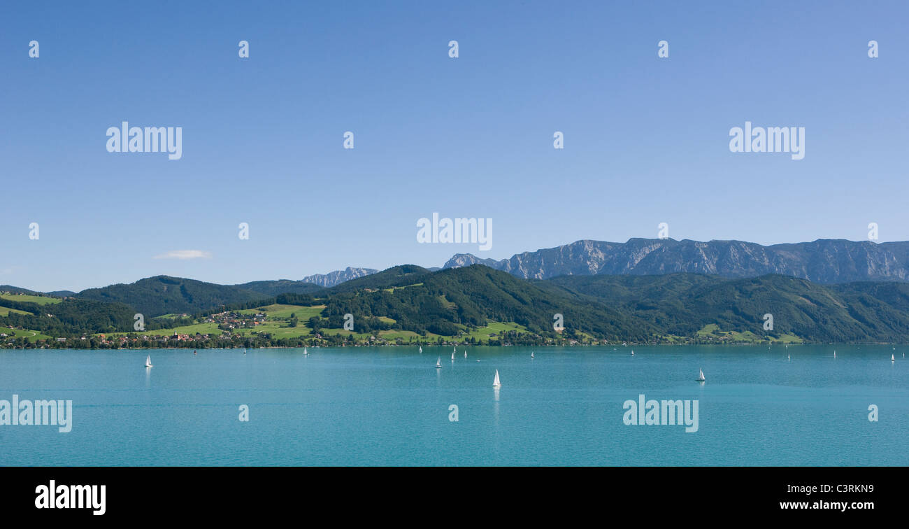 Austria, Salzkammergut, Boats in attersee lake with hoellen mountains in background - Stock Image