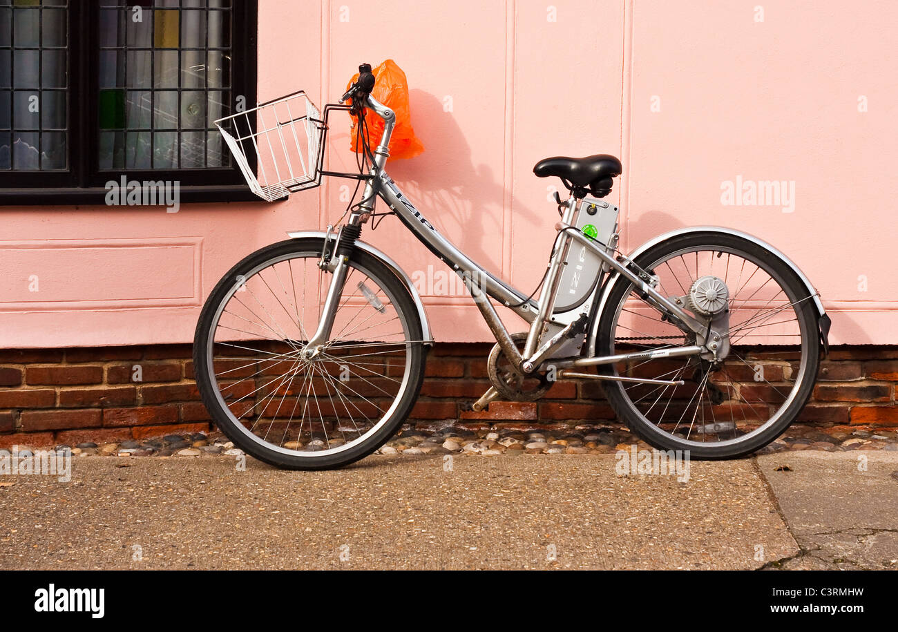 Ladies' bike leant against a pink wall - Stock Image