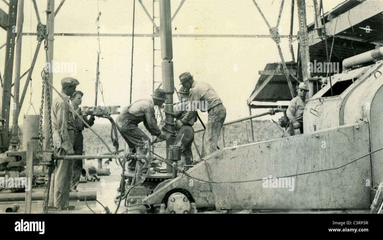 Oil workers drilling during 1938 1930s energy working glass petroleum industry field - Stock Image
