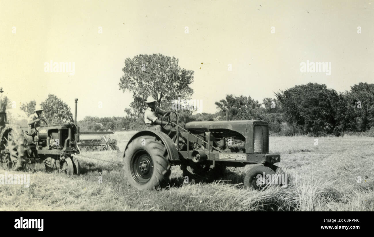 A farm laborer uses Allis Chalmers tractor to pull another during 1930s harvest - Stock Image