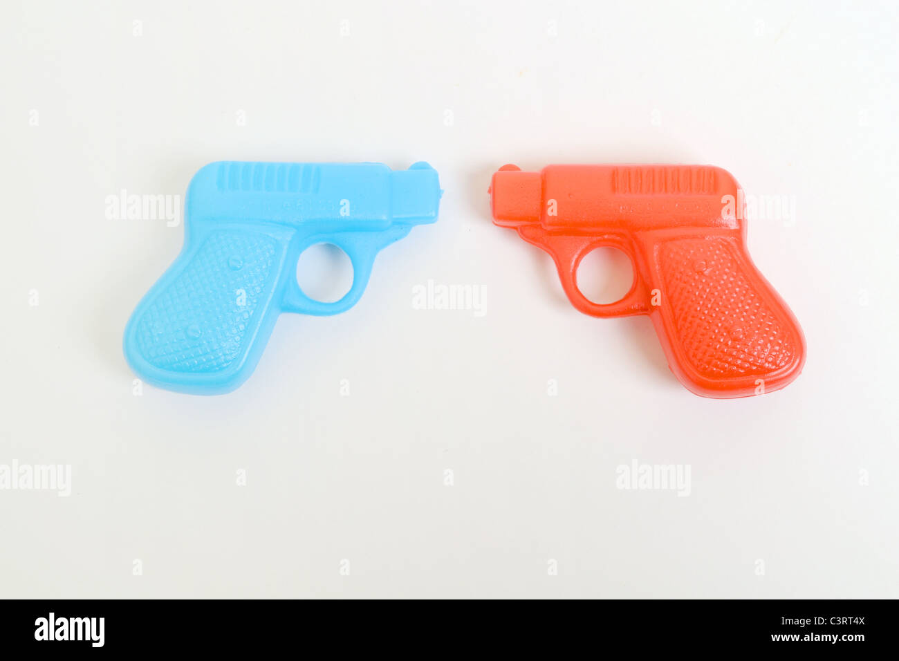 Stalemate Toy plastic guns pistols red blue colours metaphor war fighting countries genders gender nations civil - Stock Image