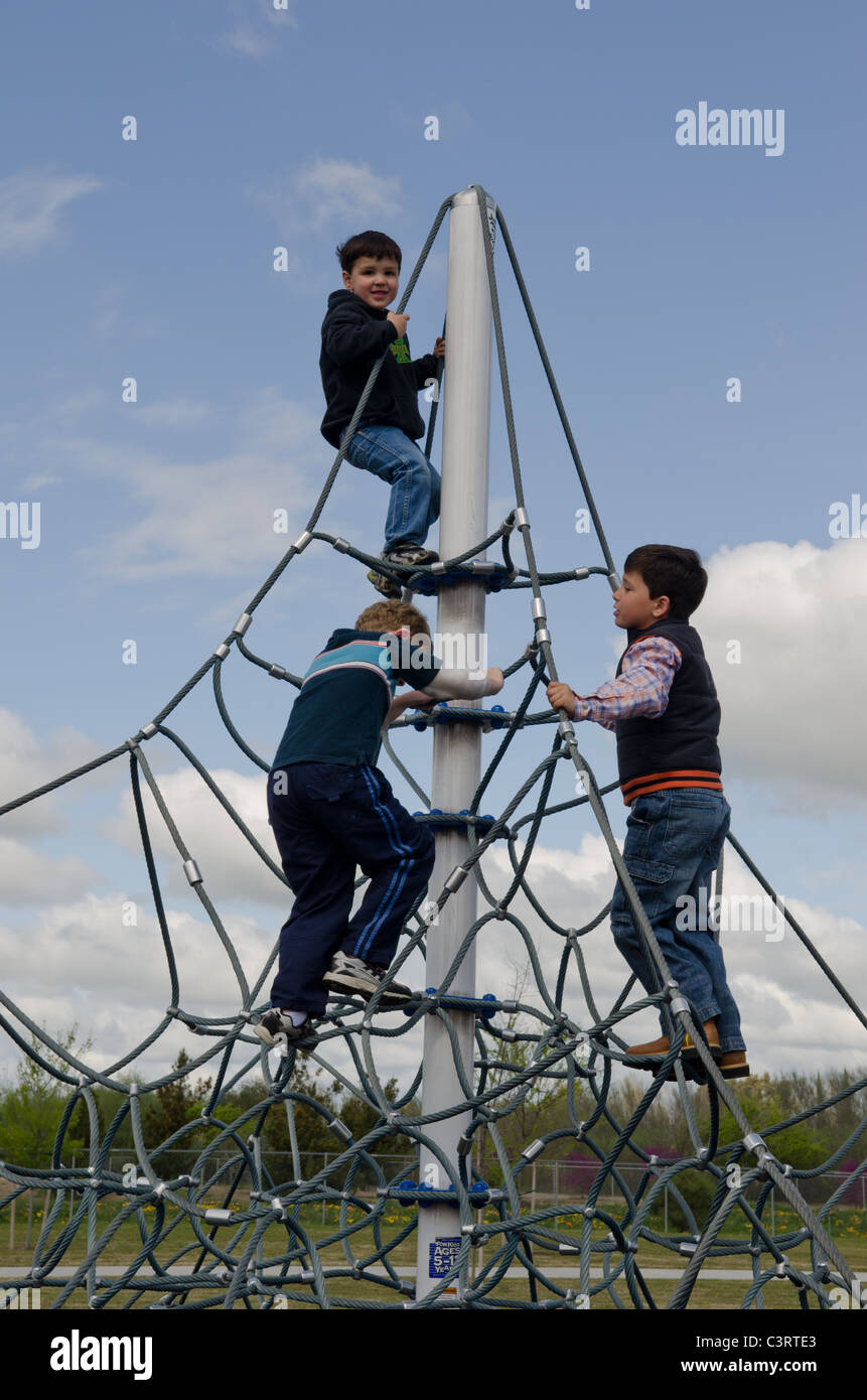 3 preschool kindergarten age children climbing on playground toy.  Model releases available for the boys whose faces - Stock Image