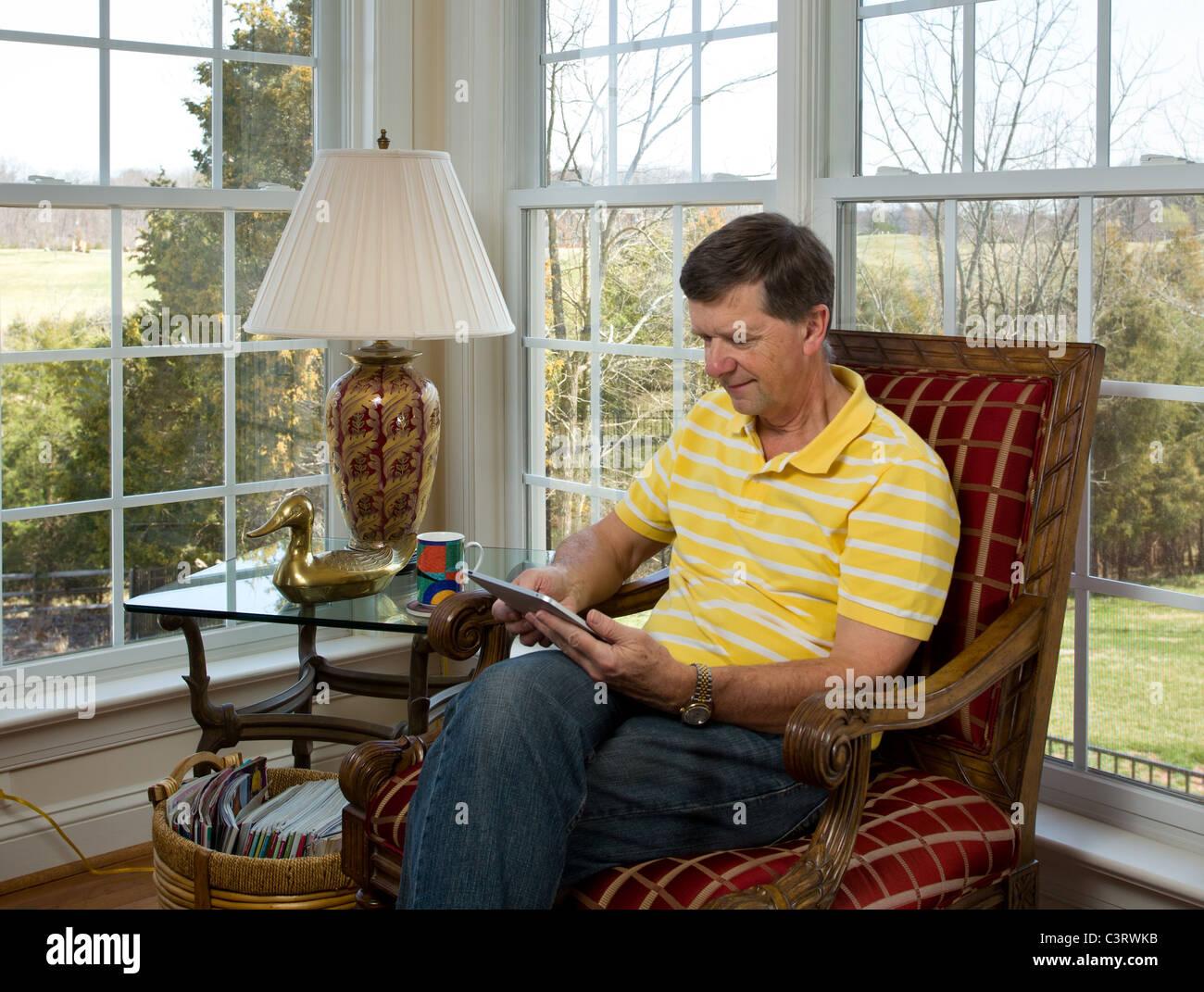 Senior man sitting at home reading on his iPad - Stock Image