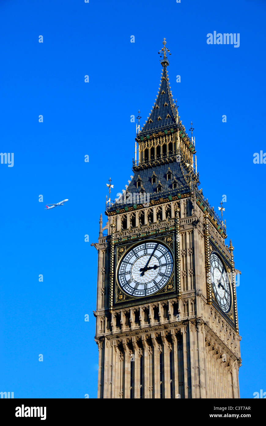 View of Big Ben clock tower at the Houses of Parliament with jet airliner passing , London, UK - Stock Image