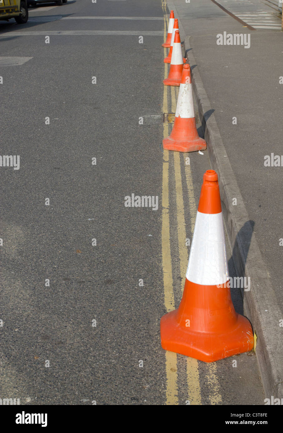 A row of 5 police traffic cones on double yellow lines. - Stock Image