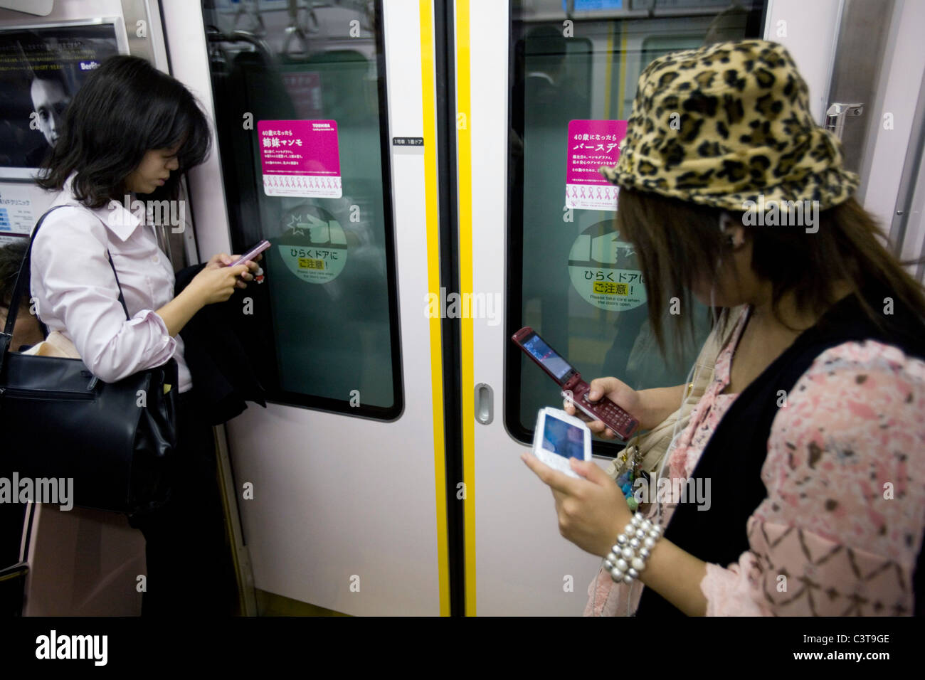 Two Japanese women using mobile phones, Tokyo, Japan Stock Photo