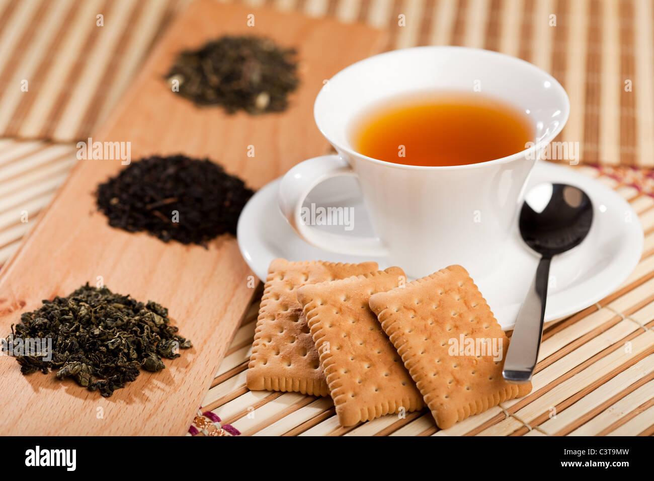A cup of tea near three piles of various kinds of tea Stock Photo