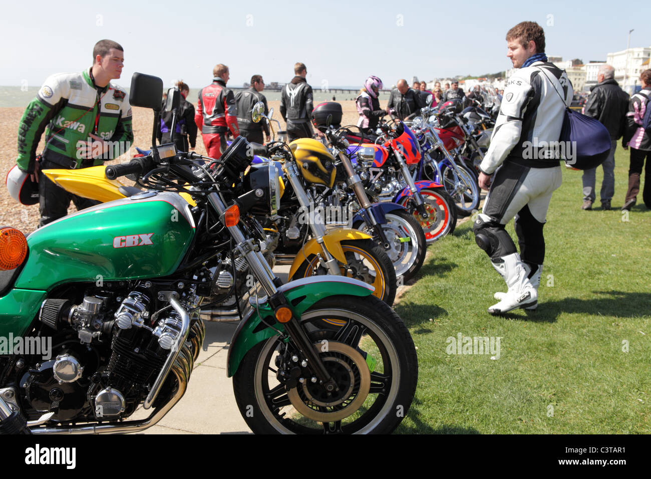 Bikers admiring motorbikes parked on Hastings seafront at the annual May Day motorbike rally 'Bike1066' - Stock Image