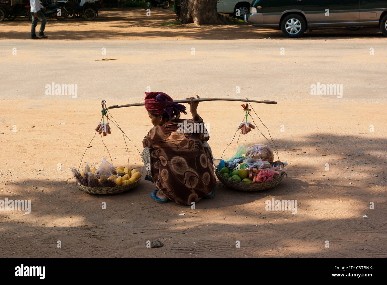 Old lady selling fruits on the street near Angkor Wat, Siem Reap, Cambodia - Stock Image