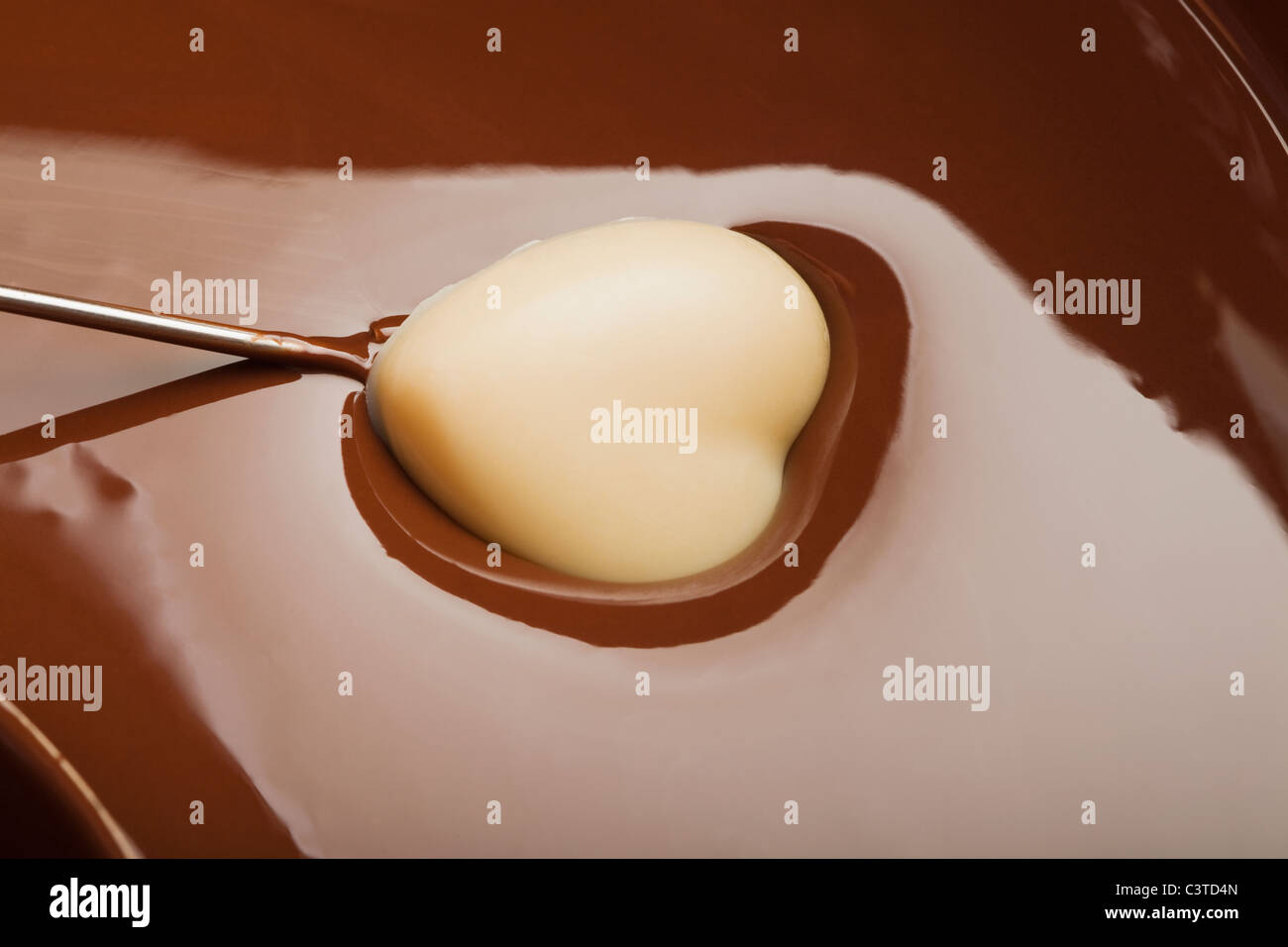 Heart-shaped candy being dipped in chocolate Stock Photo