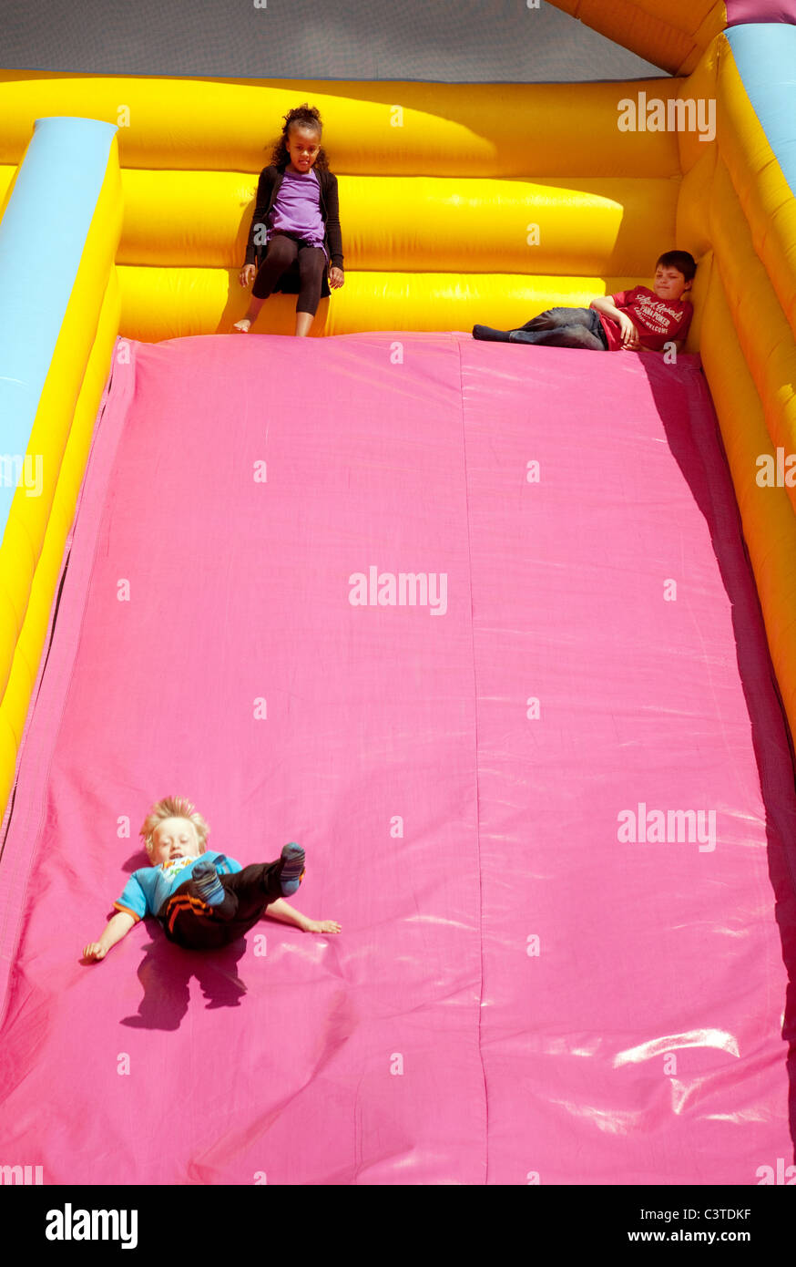 Three young children on an inflatable slide, Reach fair, Cambridgeshire UK - Stock Image