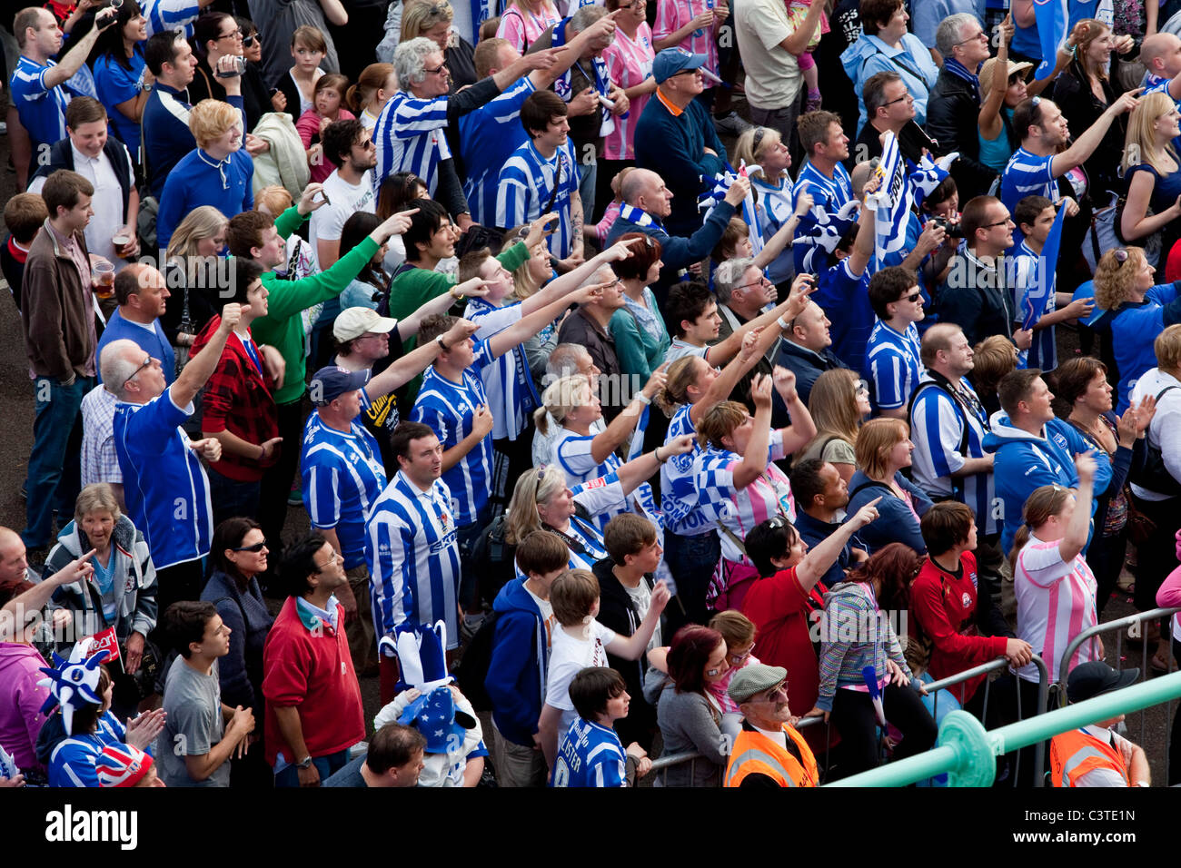 Brighton and Hove Albion Football Supporters cheer the team during the clubs victory parade along Brighton seafront. - Stock Image