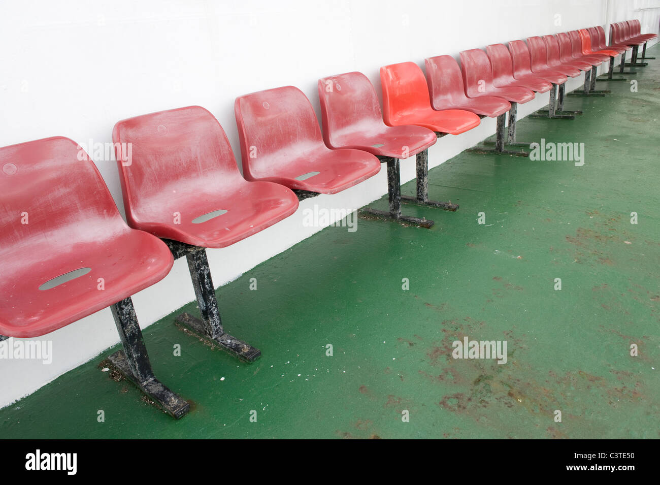 Rows of red seats on the deck of a ferry. Stock Photo