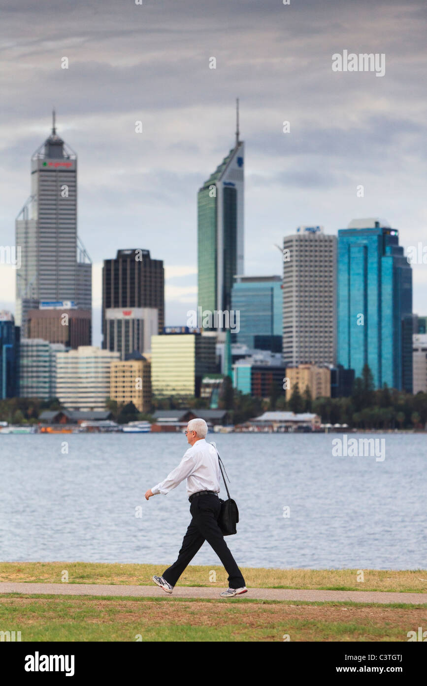 Man carrying a bag and wearing trousers, shirt and running shoes on his way to work with city skyscrapers in the - Stock Image
