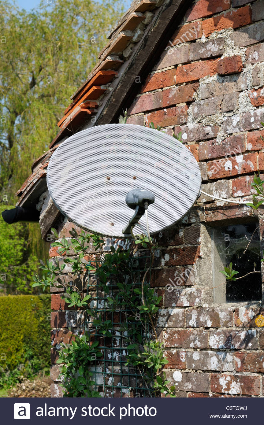 Satellite dish on out-building, England - Stock Image