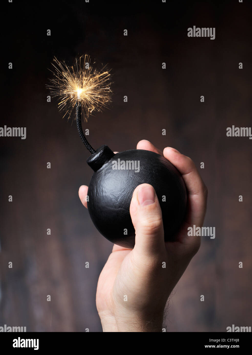 Man holding a bomb in his hand, ready for a throw - Stock Image