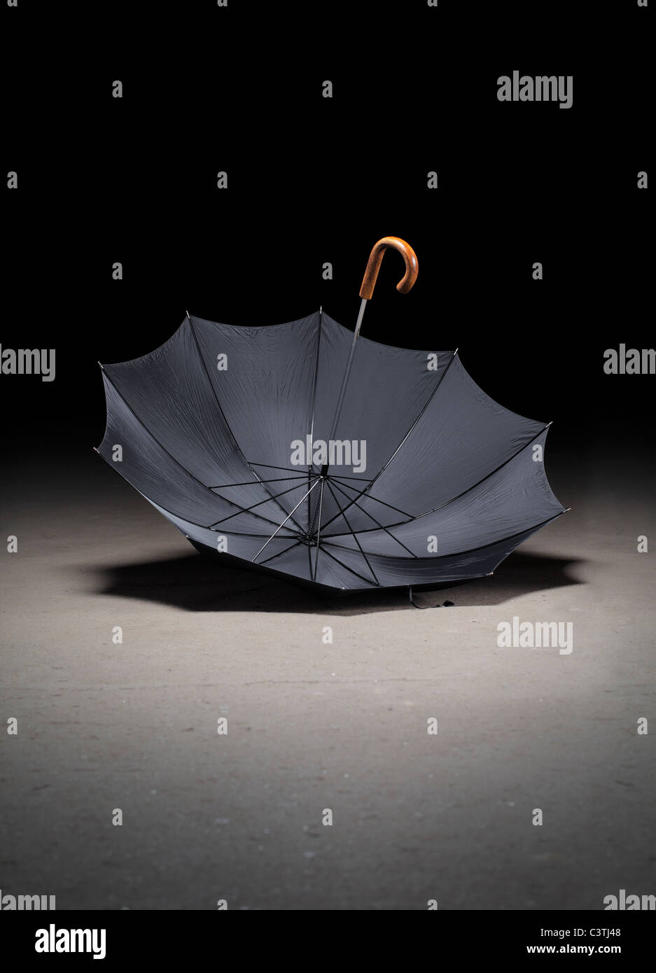 Old black umbrella upside down on dirty concrete floor - Stock Image