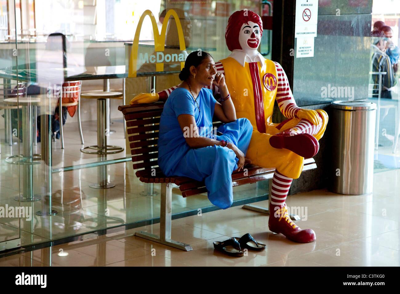 Indian woman sitting on bench at McDonald's fast food restaurant, Varanasi, Uttar Pradesh, India, Asia - Stock Image