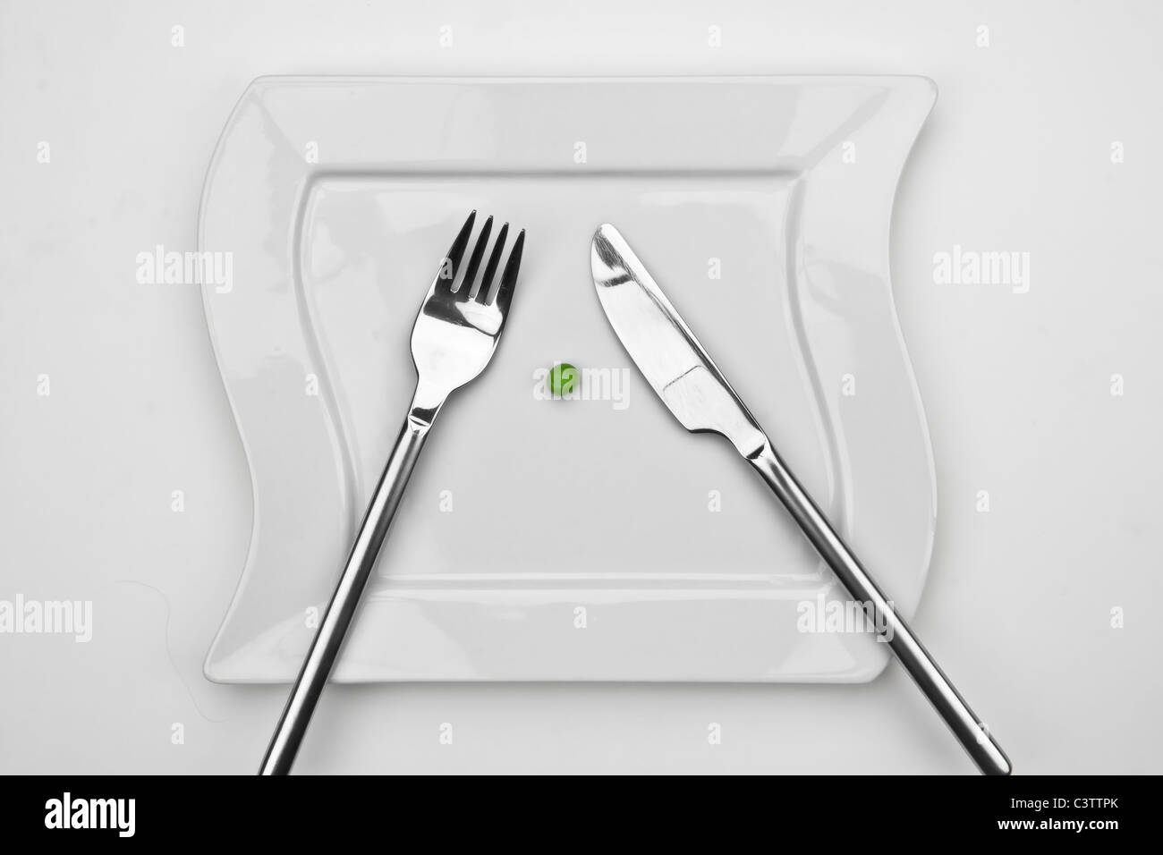 one pea on a white plate with fork and knife - Stock Image