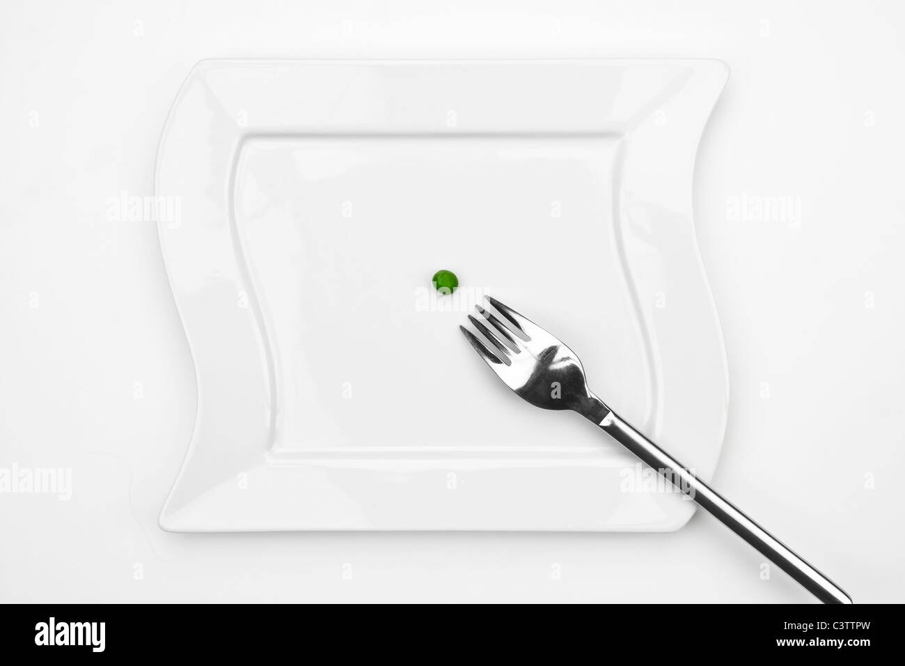one pea on a white plate with a fork - Stock Image