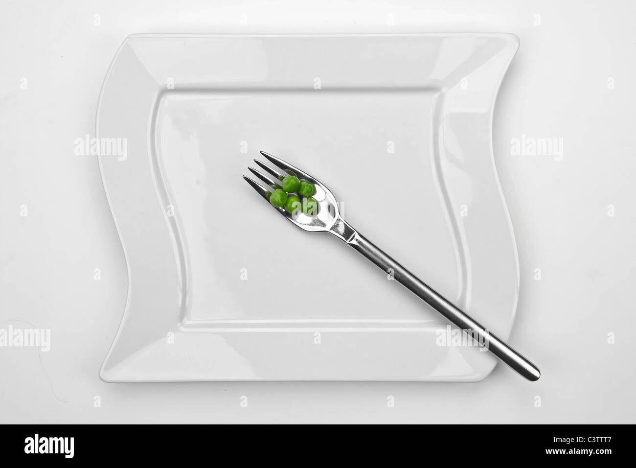 five peas on a fork with a white plate - Stock Image