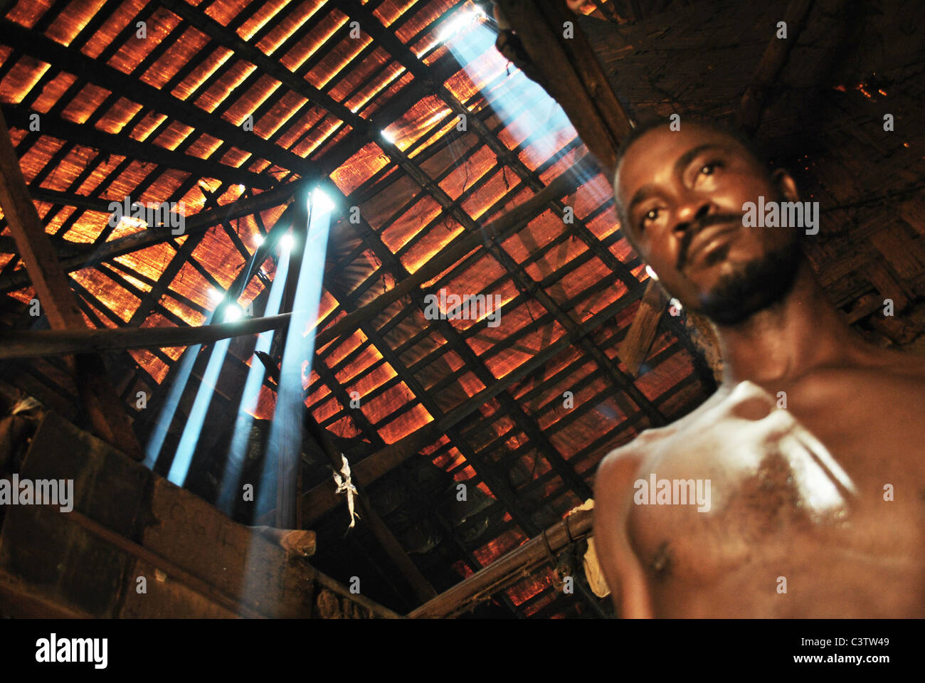 Light streams through holes in the roof of a Liberian refugee's shelter in Nicla Camp, Guiglo, Ivory Coast - Stock Image