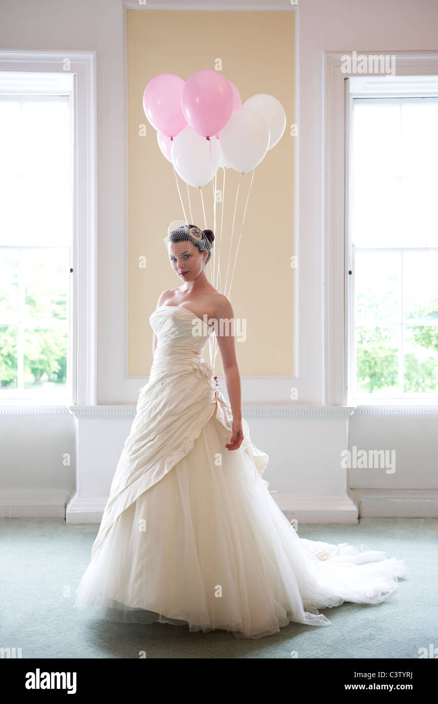 pretty bride in her wedding dress holding balloons in front of windows - Stock Image