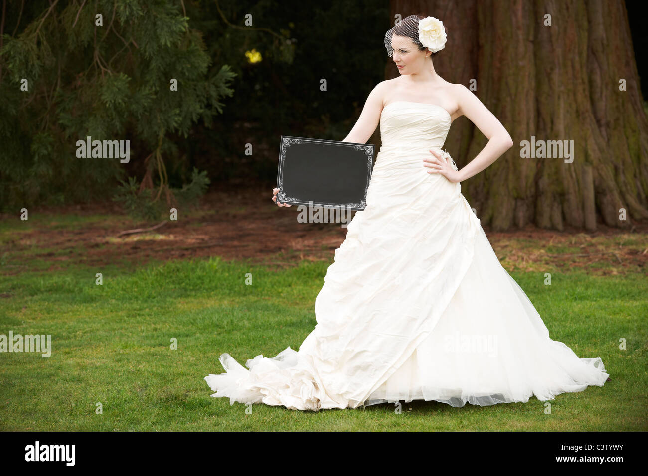 Pretty bride in wedding dress holding a blank board with space for copy - Stock Image