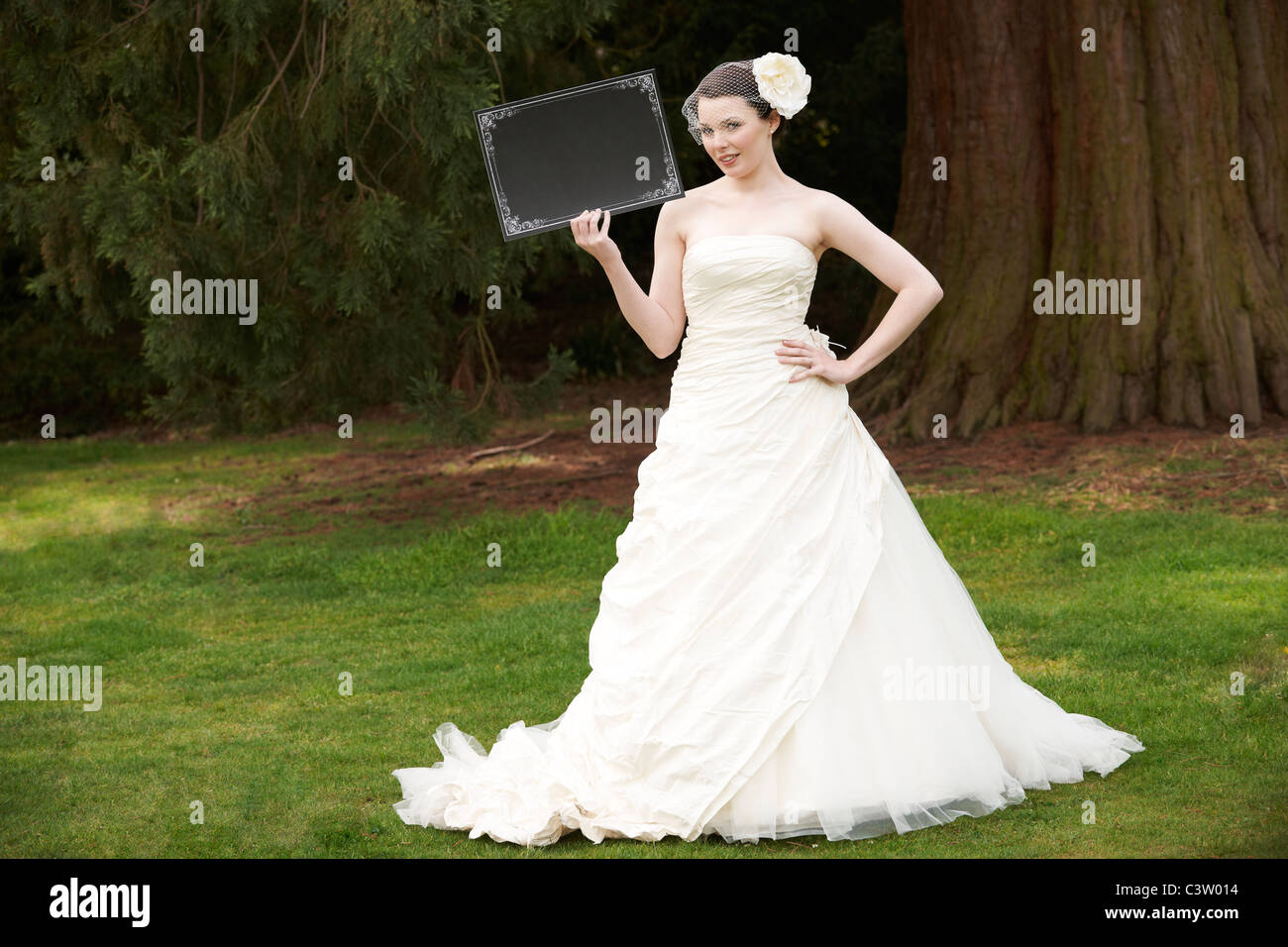 Pretty bride in wedding dress holding a blank board with space for ...