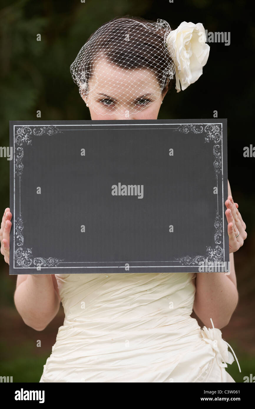 Pretty bride in wedding dress holding a blank board in front of face with space for copy - Stock Image