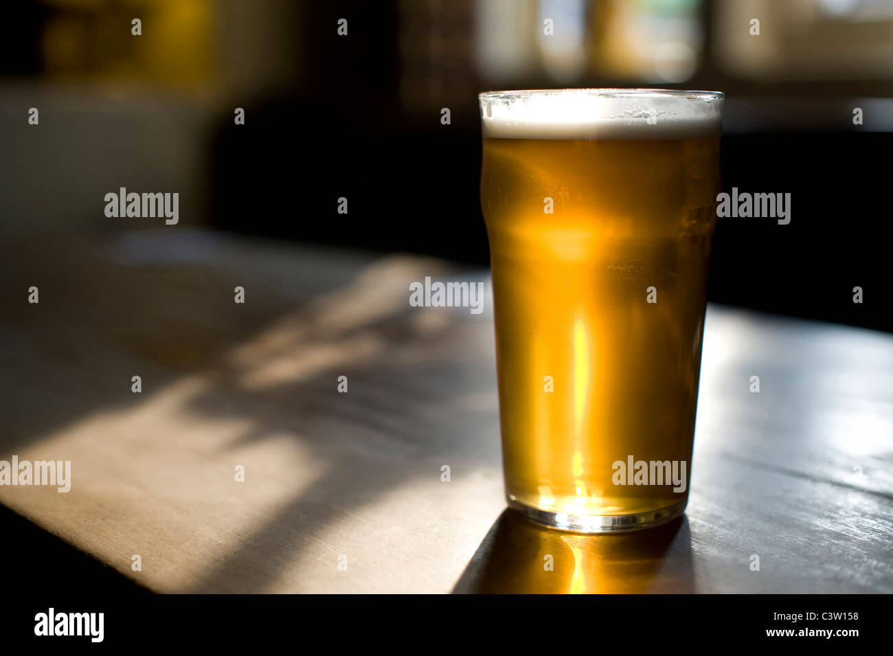 An almost full pint of real ale sits on a sunlit wooden table of a pub. - Stock Image