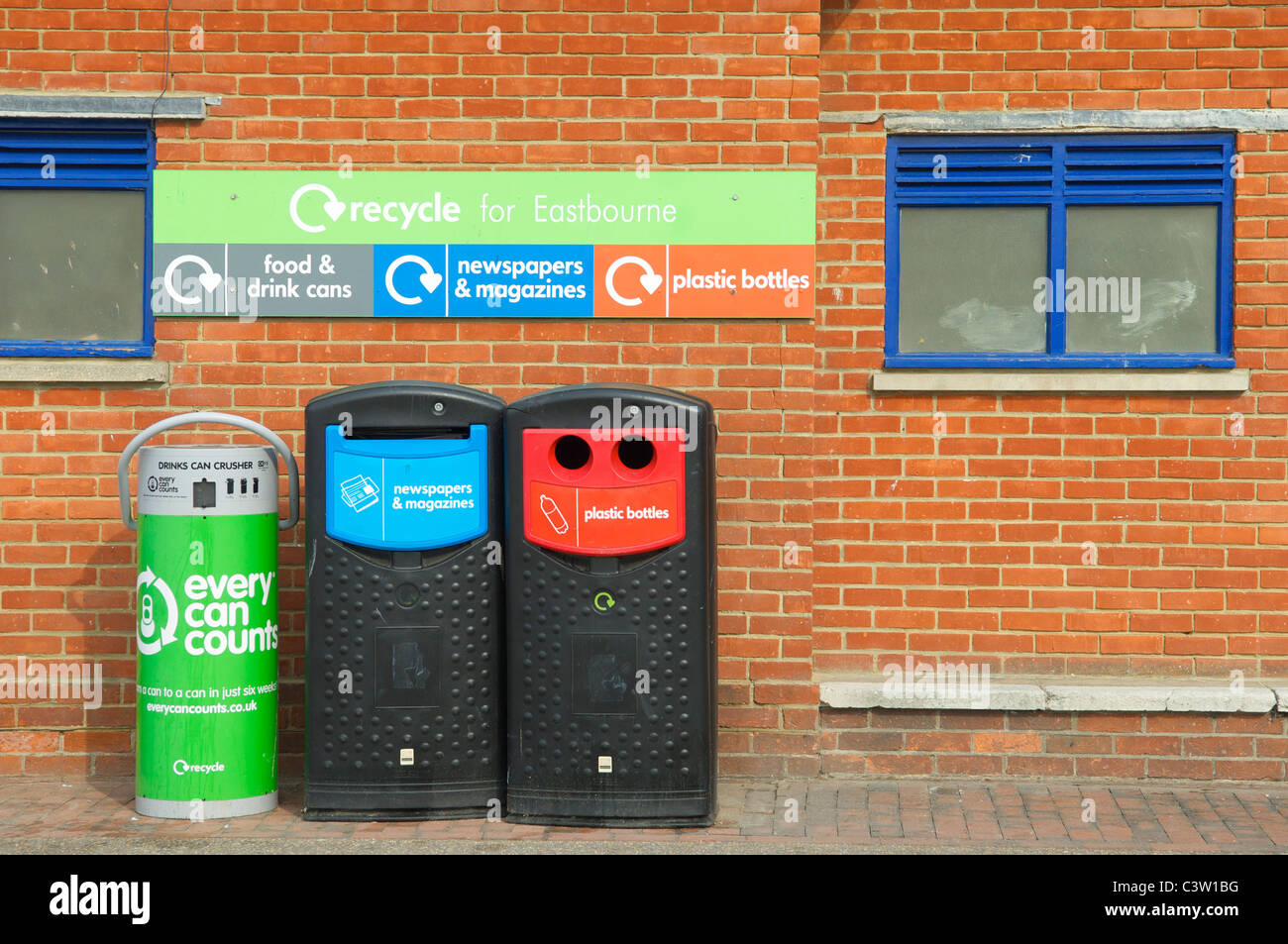 Recycling bins against brick wall Stock Photo