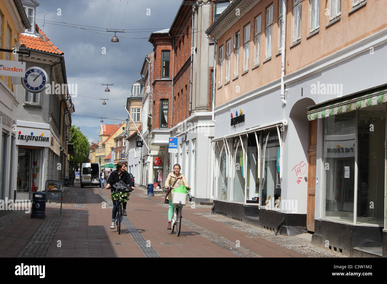Two women biking down town Helsingør, Denmark - Stock Image