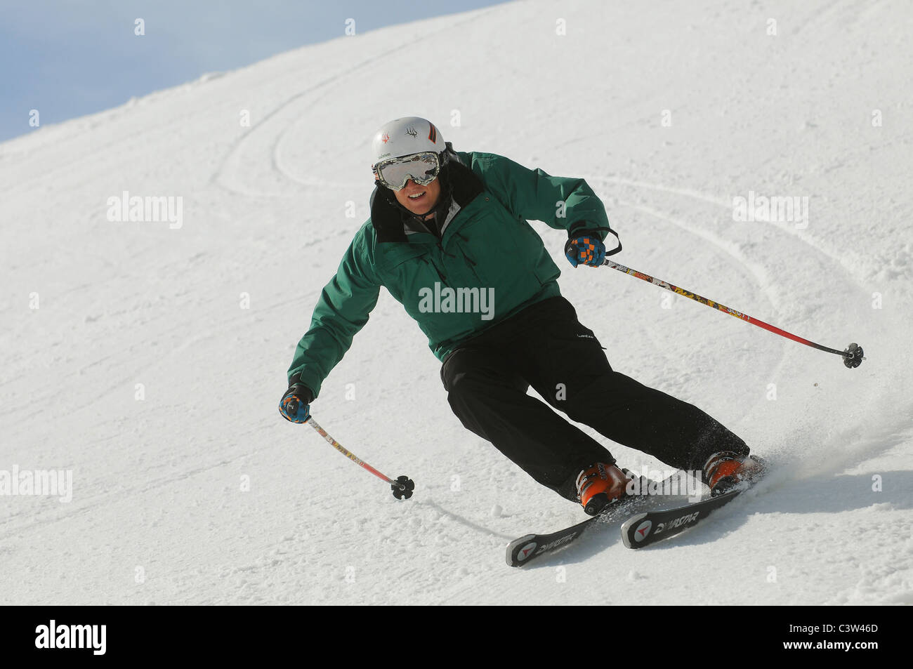 A skier carving turns on piste. - Stock Image