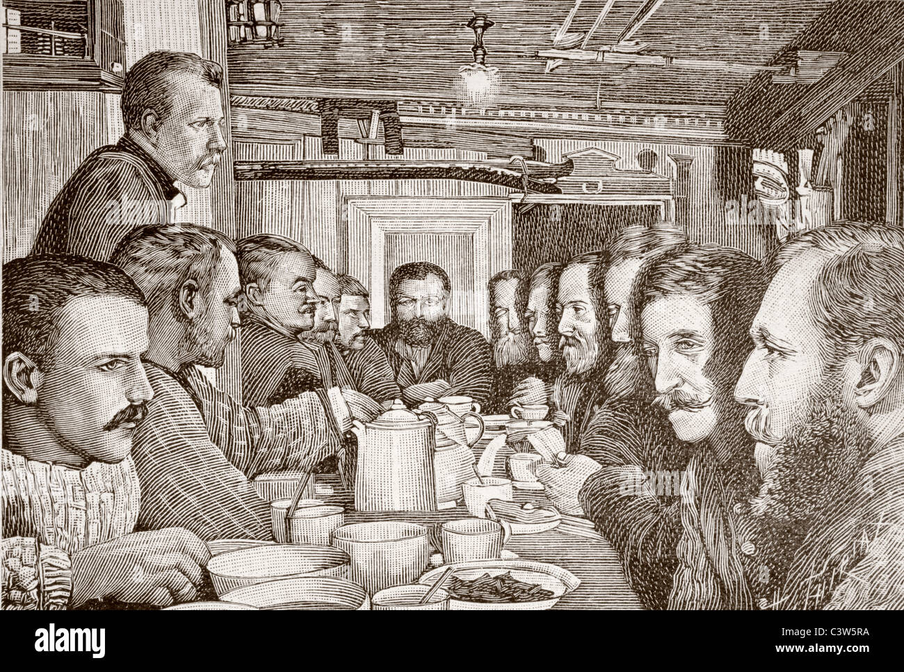 Nansen, standing left, speaks to the twelve men of his team in the galley of the Fram during the Fram polar expedition. - Stock Image