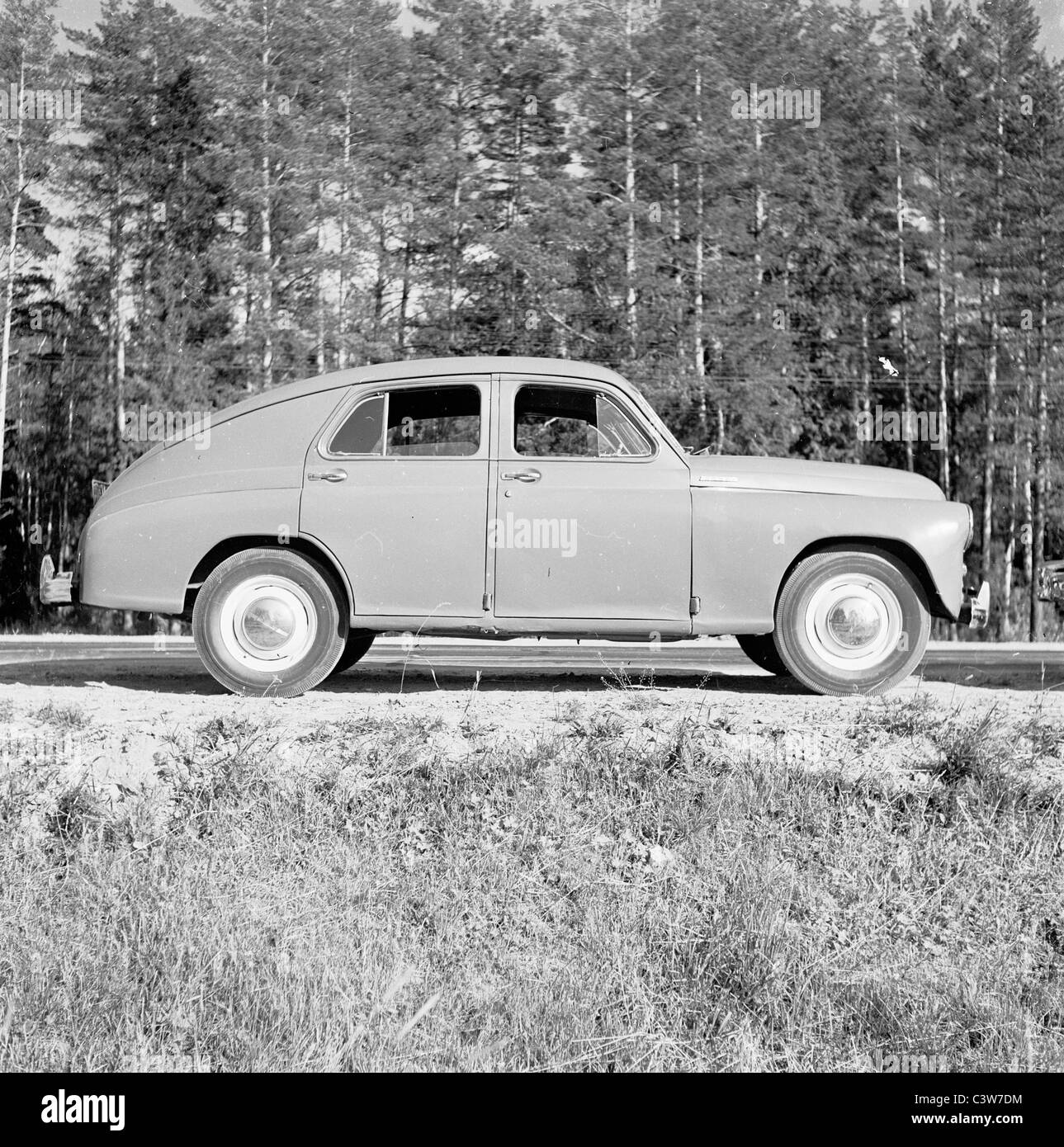 1950s. An historical picture by J Allan Cash of a Pobeda car parked on a road in the forest in Georgia. - Stock Image