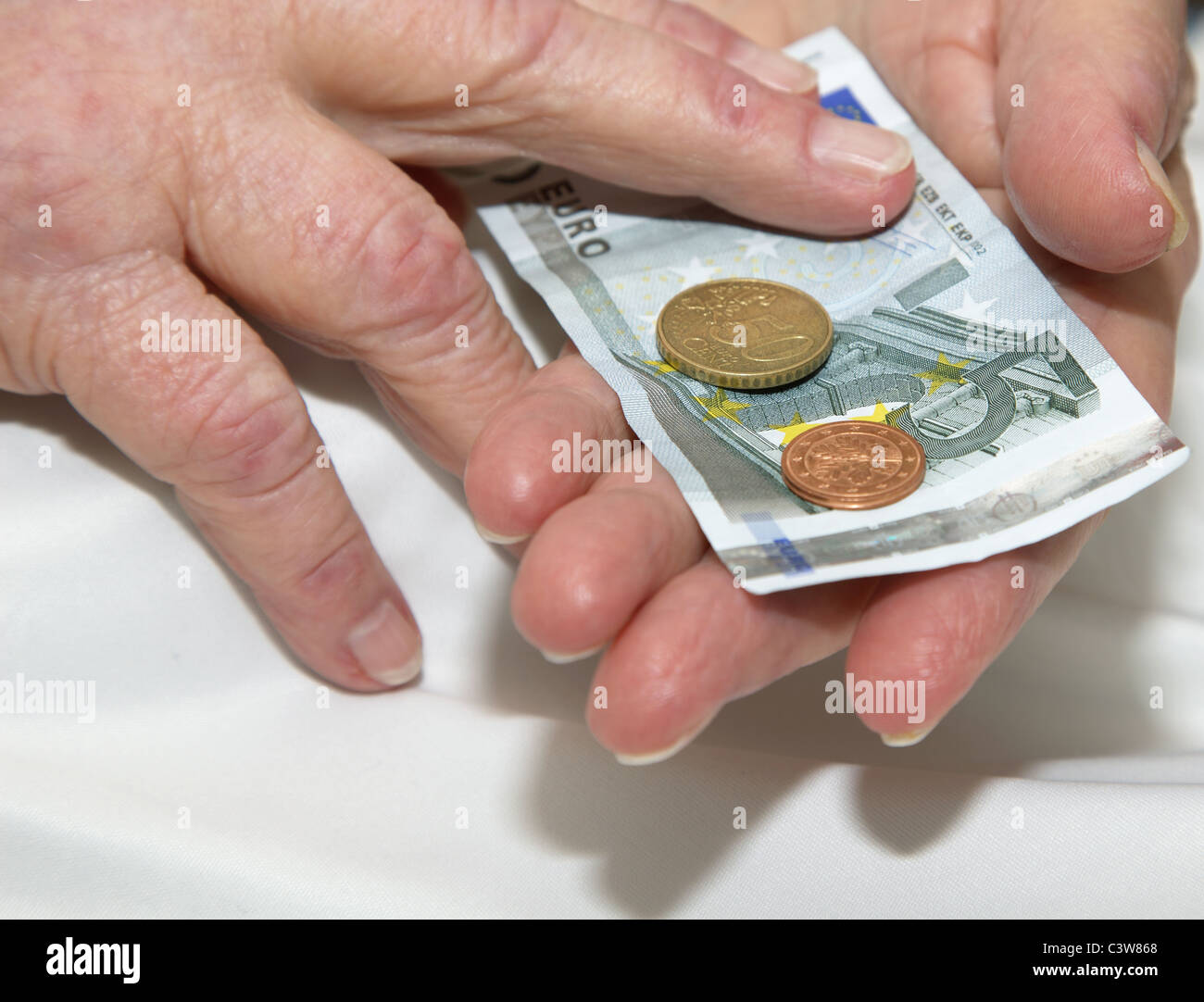 Wrinkled hands of a care-dependent person holding some euro. - Stock Image