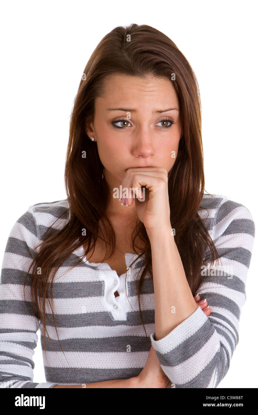 Worried young woman holds her fist to her face and wrinkles up her forehead in worry. - Stock Image