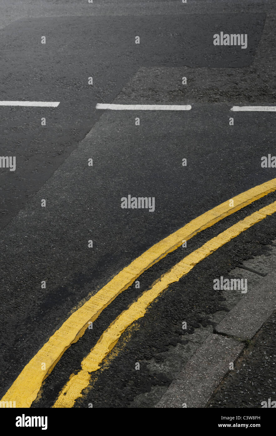 Curved Double Yellow Lines on the Road at a Junction - Stock Image
