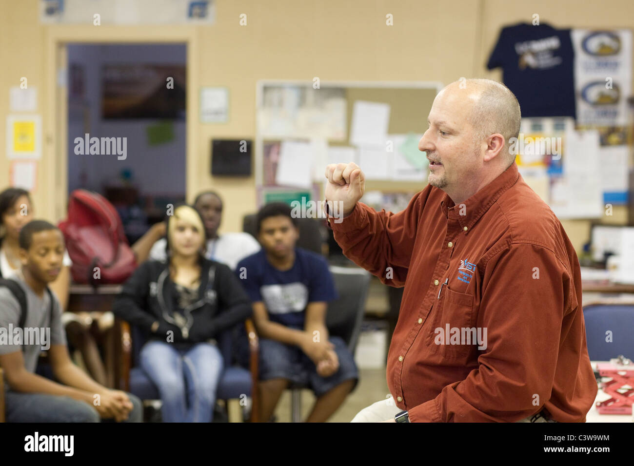 Male Anglo teacher talks to an ethnic and racial mix of students at Rapoport Academy public charter high school - Stock Image