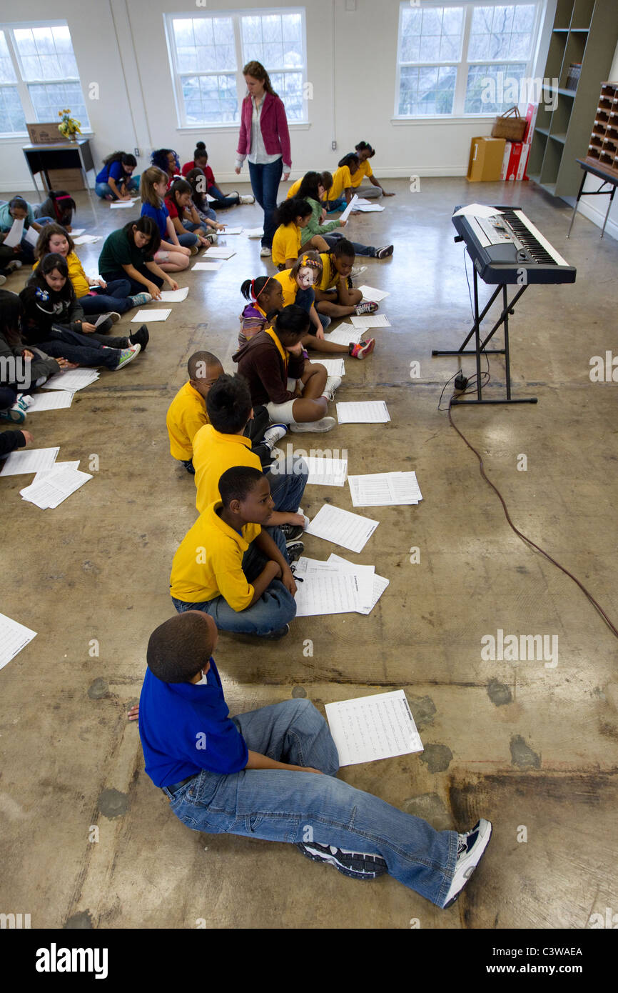multi-ethnic group of students read sheet music before singing in music class at Rapoport Academy public charter Stock Photo