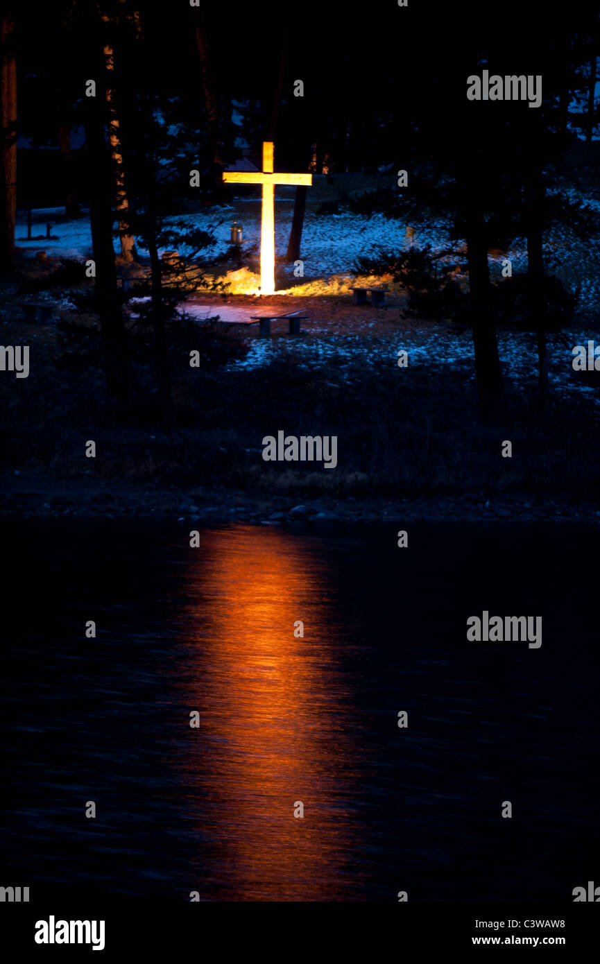A spotlit cross is reflected at night in the calm water of Salmon Lake, Montana - Stock Image