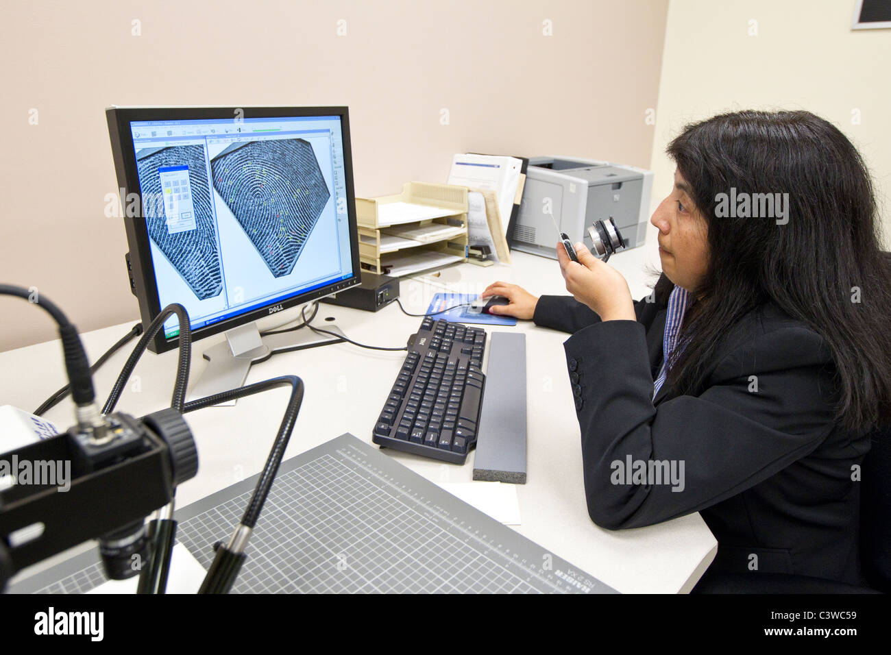 A Texas Dept. of Public Safety (DPS) employee compares fingerprints from a national criminal database to latent - Stock Image