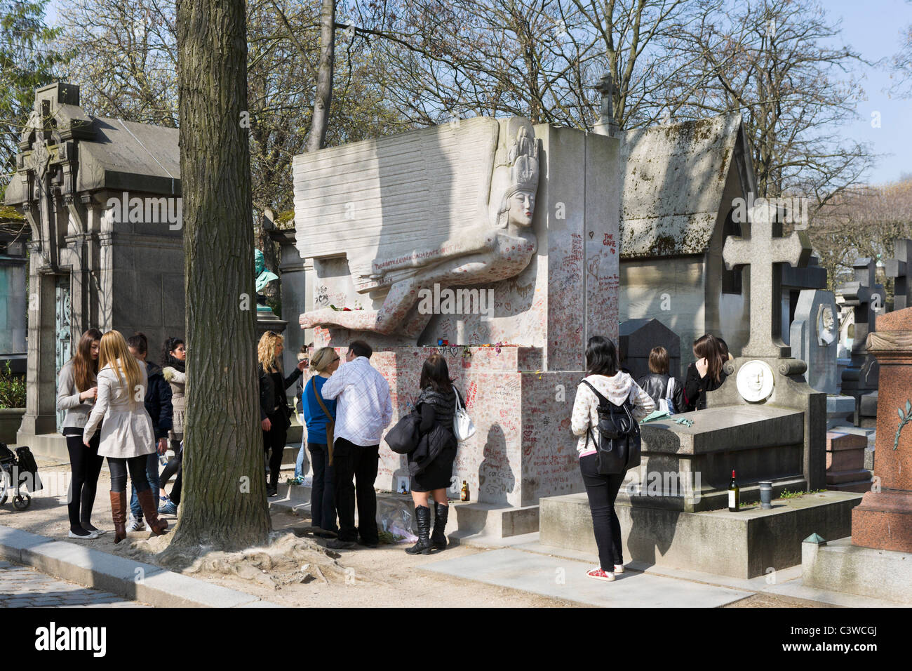 Tourists surrounding the tomb of the writer Oscar Wilde in Pere Lachaise Cemetery, 20th Arrondissement, Paris, France - Stock Image